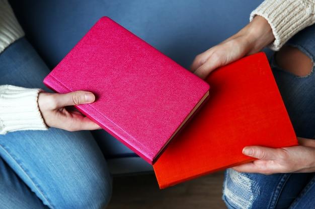 Mulher dando livro para mulher, no fundo da mesa de madeira