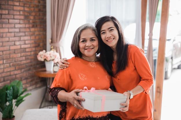 Mulher dando presente para sua mãe idosa