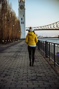 Mulher dando um passeio em um parque perto da ponte jacques cartier, no canadá