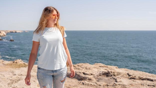 Mulher dando um passeio na praia com espaço de cópia