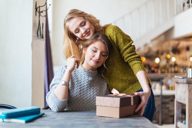 Mulher dando um presente para a namorada no café