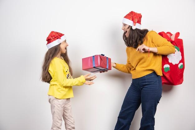 Mulher dando um presente para uma jovem com chapéu de papai noel vermelho.