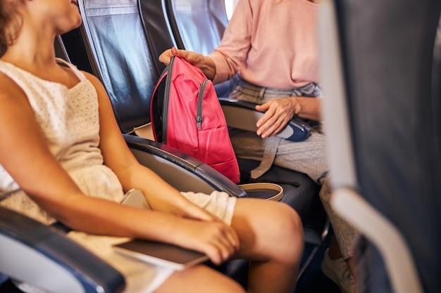 Mulher dando uma mochila escolar para uma garota