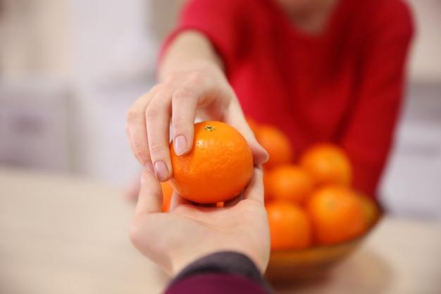 Mulher dando uma tangerina para um homem