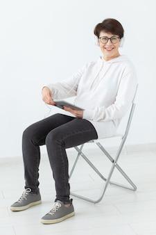 Mulher de 40-50 anos de idade no fone de ouvido, sentada na cadeira e segurando o tablet.