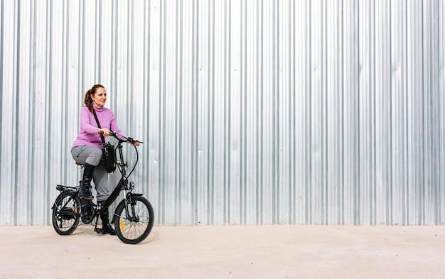 Mulher de 40 anos andando de bicicleta elétrica pelas ruas da cidade (conceito de mobilidade elétrica)