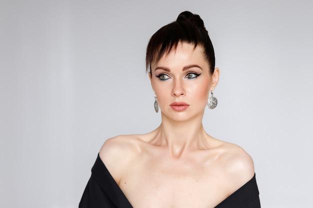 Mulher de 40 anos com a pele limpa no minimalismo branco