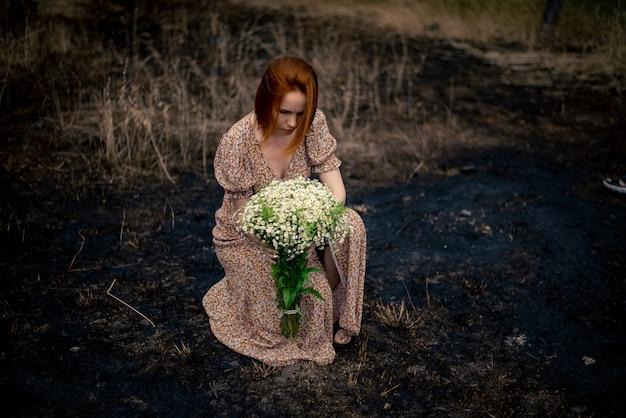 Mulher de 40 anos com um buquê de flores silvestres na terra arrasada, conceito de esgotamento psicológico