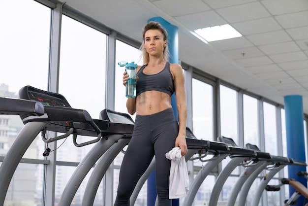 Mulher de academia malhando água potável em pé por máquinas de fitness