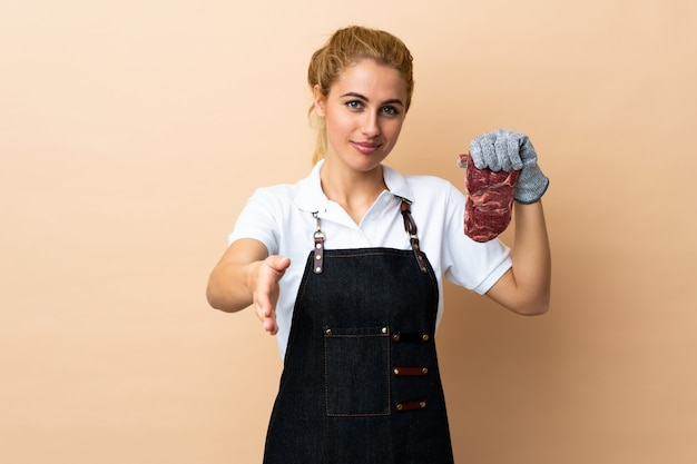 Mulher de açougueiro vestindo um avental e servindo carne cortada fresca sobre aperto de mão isolado depois de um bom negócio