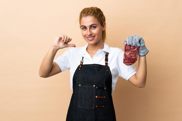 Mulher de açougueiro vestindo um avental e servindo carne fresca cortada sobre parede isolada orgulhoso e satisfeito