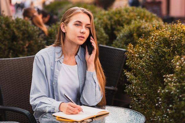 Mulher de alto ângulo, anotando na agenda
