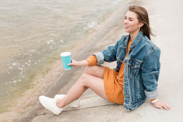Mulher de alto ângulo com café à beira-mar