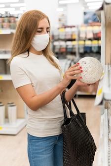 Mulher de alto ângulo com máscara de compras