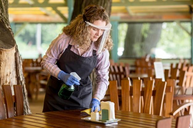 Mulher de alto ângulo com proteção facial limpando mesas