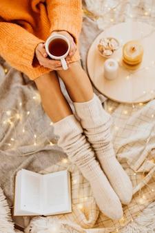 Mulher de alto ângulo curtindo as férias de inverno com uma xícara de chá