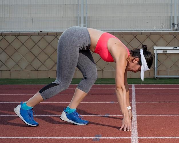 Mulher de alto ângulo em posição de corrida