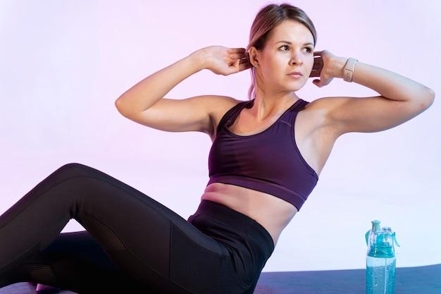 Mulher de alto ângulo fazendo exercício abdominal
