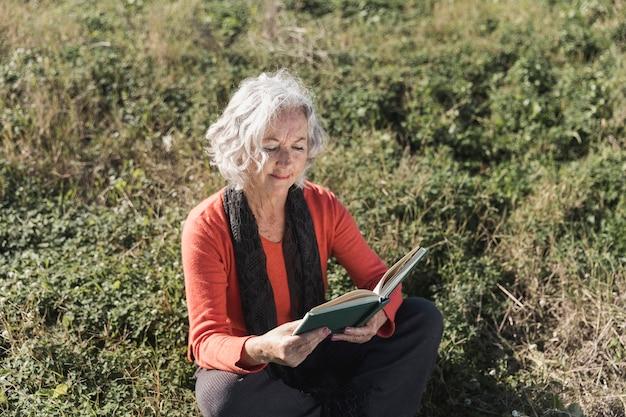 Mulher de alto ângulo lendo ao ar livre