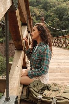 Mulher de alto ângulo na borda da ponte sentado