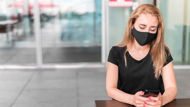 Mulher de alto ângulo no shopping usando máscara