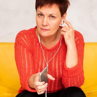 Mulher de alto ângulo no sofá ouvindo música