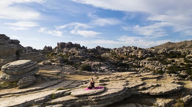Mulher de alto ângulo no topo da prática de montanha