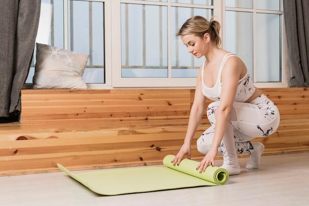 Mulher de alto ângulo rolando tapete de ioga