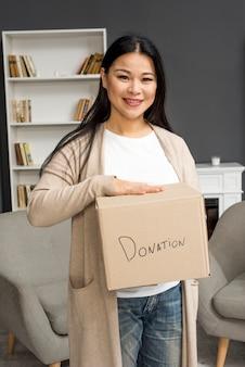 Mulher de alto ângulo, segurando a caixa de doações