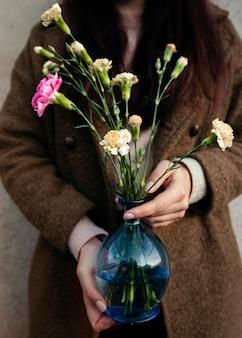 Mulher de alto ângulo, segurando o vaso com flores