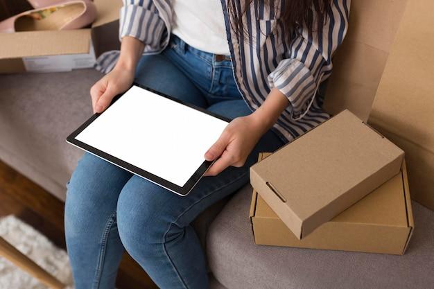 Mulher de alto ângulo segurando um tablet de tela vazia