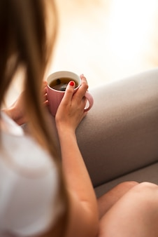 Mulher de alto ângulo, segurando uma xícara de chá