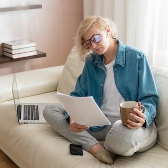 Mulher de alto ângulo, trabalhando no sofá e tomando café