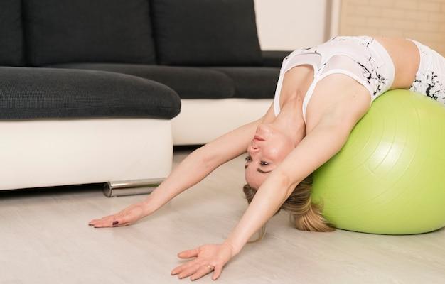 Mulher de alto ângulo treinando com bola de fitness em casa