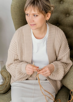 Mulher de alto ângulo tricotando por dentro