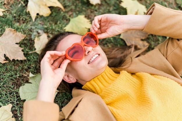 Mulher de alto ângulo, usando óculos em forma de coração ao lado de folhas de outono