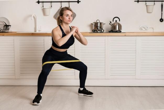 Mulher de ângulo alto, treinamento com elástico