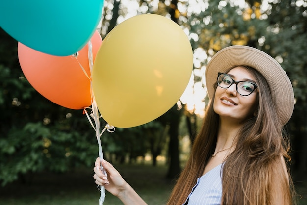 Mulher de aniversário com chapéu, olhando para a câmera