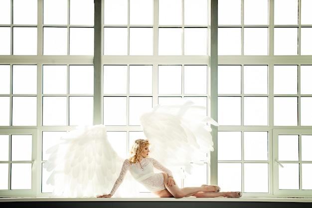 Mulher de anjo branco com asas de penas