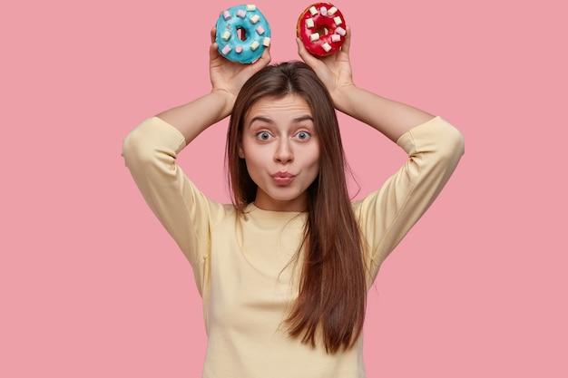 Mulher de aparência agradável com cabelo escuro e liso, segura deliciosos donuts acima da cabeça, vestida com roupas amarelas, modela o espaço rosa, faz beicinho