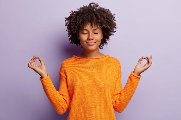 Mulher de aparência agradável e calma medita dentro de casa, segura as mãos em gesto de mudra, tem um sorriso encantador, olhos fechados, usa roupas laranja, modelos sobre parede roxa. gesto de mão. conceito de meditação
