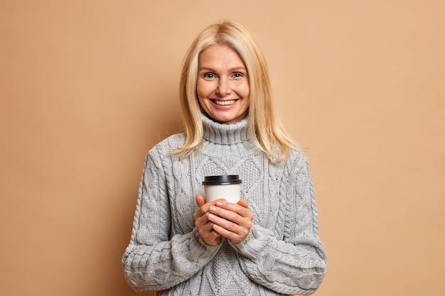 Mulher de aparência agradável positiva com cabelo loiro segurando uma xícara descartável de café gosta de beber uma bebida quente durante o clima frio de inverno, vestida com uma camisola de malha cinza.