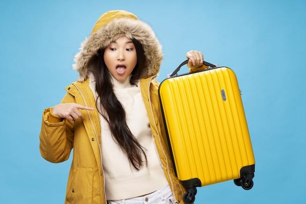 Mulher de aparência asiática em mala amarela de casaco de inverno no turismo de destino de viagem de férias