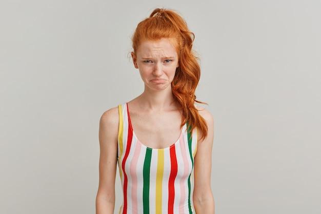 Mulher de aparência chateada, garota ruiva infeliz com rabo de cavalo e sardas, vestindo maiô colorido listrado