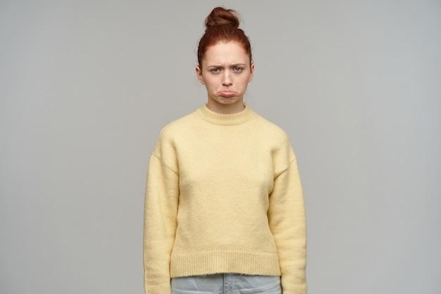 Mulher de aparência chateada, triste garota ruiva com coque de cabelo.