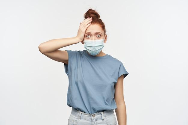 Mulher de aparência chocada e estressada com cabelo ruivo preso em um coque. vestindo camiseta azul e máscara protetora. tocando sua cabeça, esqueça algo. isolado sobre a parede branca
