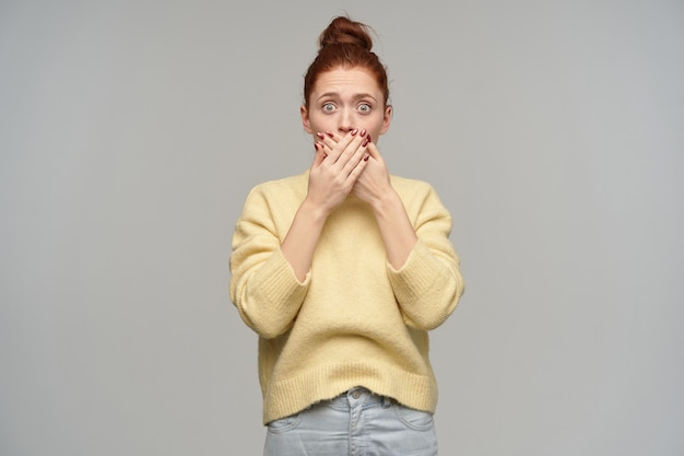 Mulher de aparência chocada, linda garota com cabelo ruivo preso em um coque. vestindo jeans e suéter amarelo pastel. cubra sua boca com as palmas das mãos. isolado sobre parede cinza