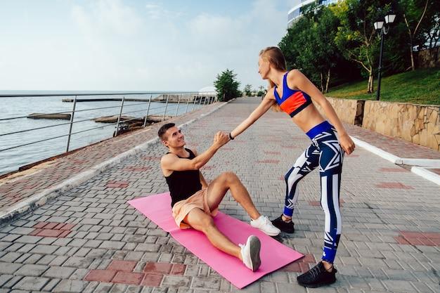 Mulher de aptidão ajuda um esportista feliz se levantar depois de fazer um exercício de esporte