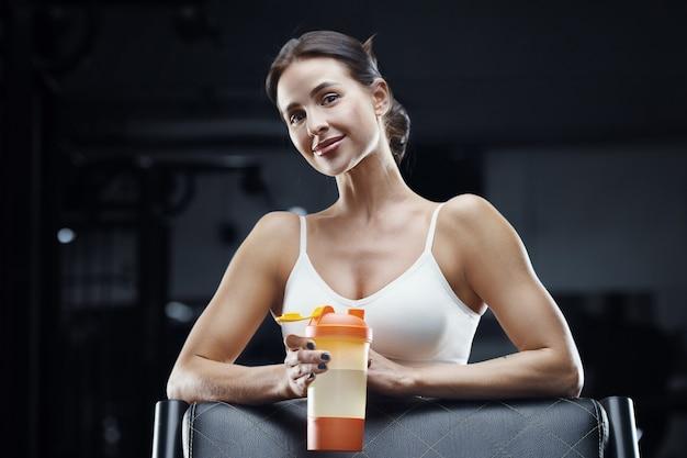 Mulher de aptidão atlética bebendo água do agitador de laranja no treino no ginásio. menina bonita caucasiana atlética. conceito de fitness e esporte. Foto Premium