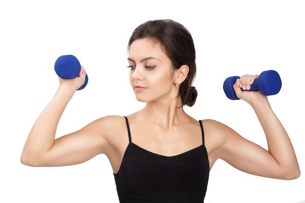 Mulher de aptidão atlética levantando halteres azuis em branco